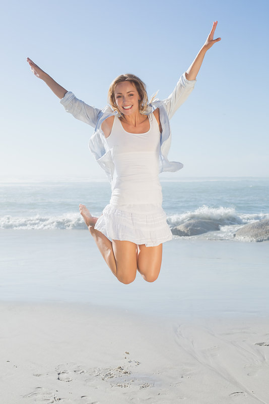 Smiling blonde leaping by the sea on a sunny day